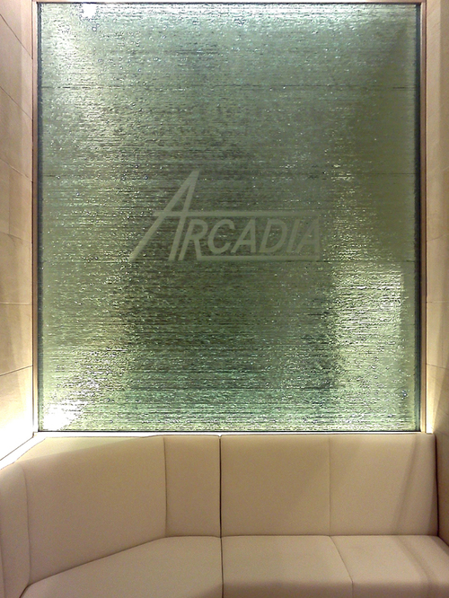 積層ガラスの背面には、ミラーを設置しています。 積層ガラスの奥行きは25mmですが、ミラーの効果で、奥行きが生まれ、 待合室の空間に広がりが出ました。 積層ガラスの小口にはいっているARCADIAというロゴが浮き上がるように見え、綺麗です。