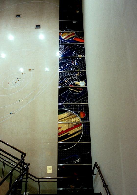 プラネタリウムがあり、夜間利用者が多い施設のため、間接光での見え方にも留意しました。アンティークガラスが暗色なるぶん、金箔や銀箔、真鍮板のほか、ところどころにオパックガラスを使用して、星のきらめきを表現しました。(右側のパネル)