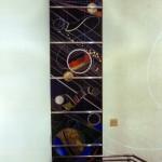 プラネタリウムがあり、夜間利用者が多い施設のため、間接光での見え方にも留意しました。アンティークガラスが暗色なるぶん、金箔や銀箔、真鍮板のほか、ところどころにオパックガラスを使用して、星のきらめきを表現しました。(左側のパネル)